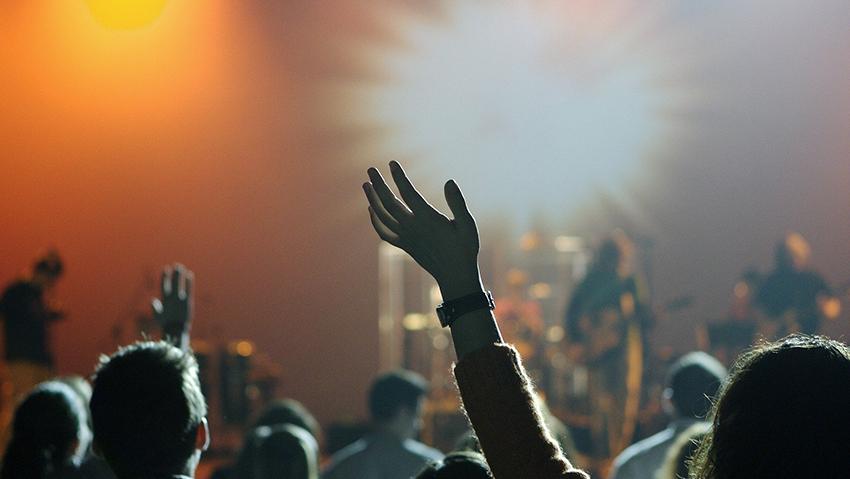 Yleisöstä kohti esiintymislavaa kuvattu kuva. Lavalla soittaa bändi.