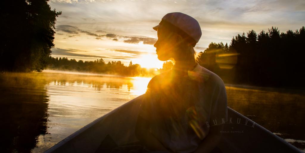 Veneilijä järvellä. Taustalla auringonlasku.